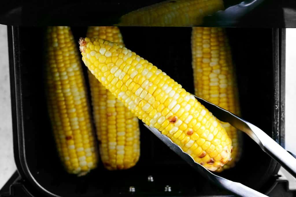 tongs holding an ear of fried corn