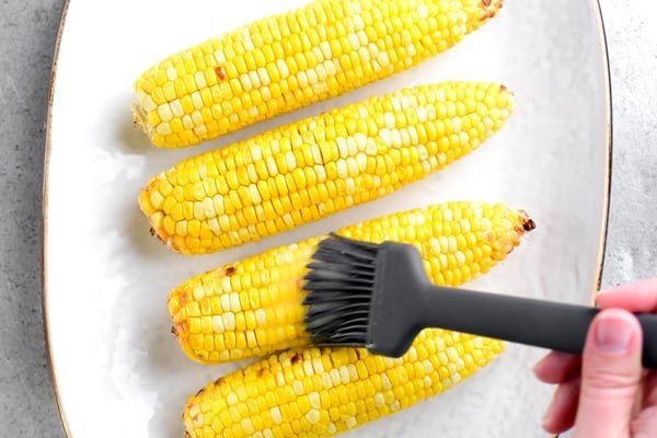 brushing butter on sweet corn