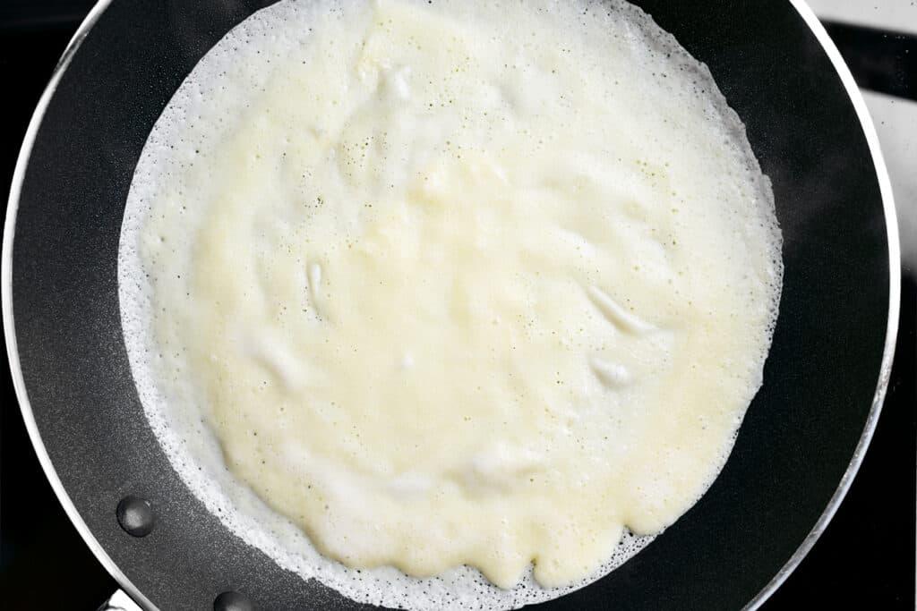 crepe batter in a frying pan