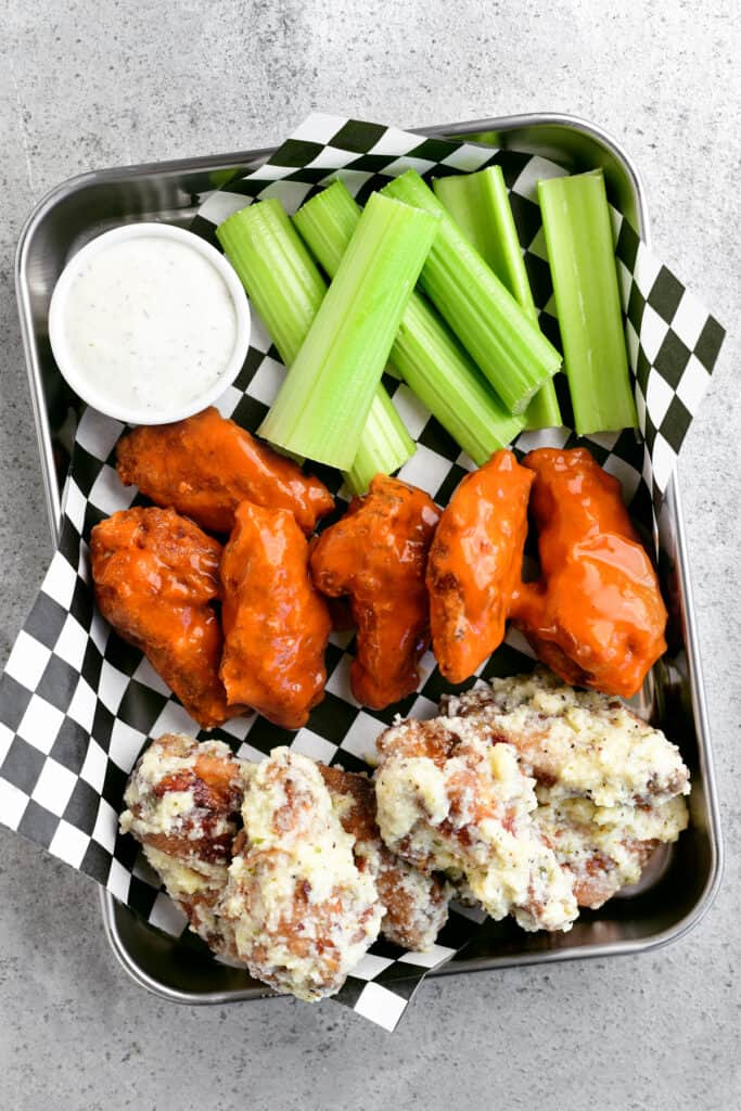 several chicken wings on a serving tray with dip and celery