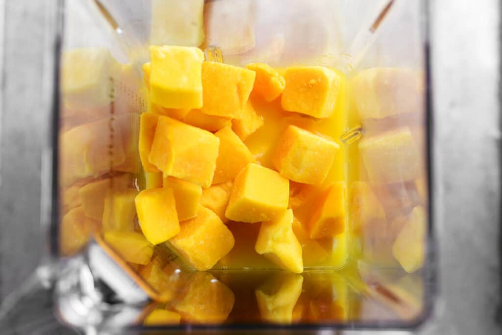 cubed mango pieces in a blender cup