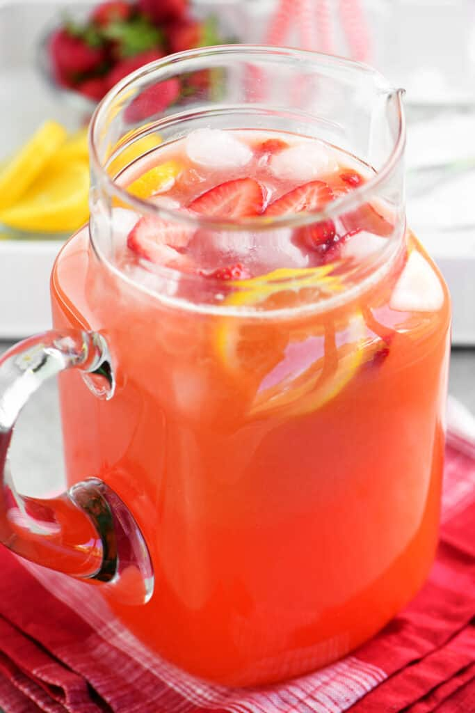 a glass pitcher with lemonade, strawberries and lemons inside