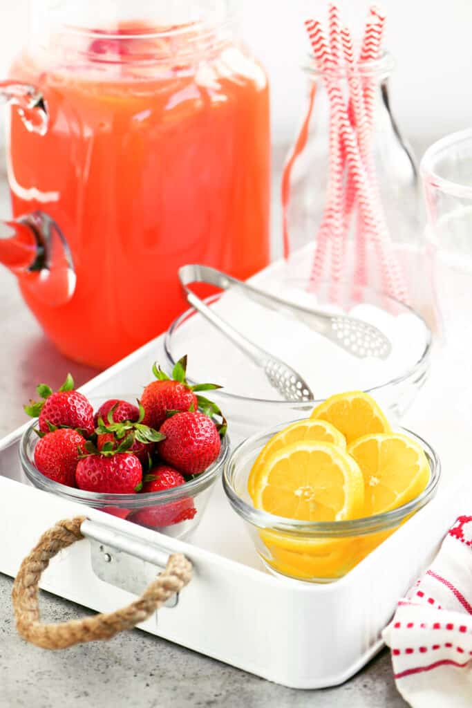 strawberry lemonade in a pitcher next to a tray with strawberries and lemons and ice