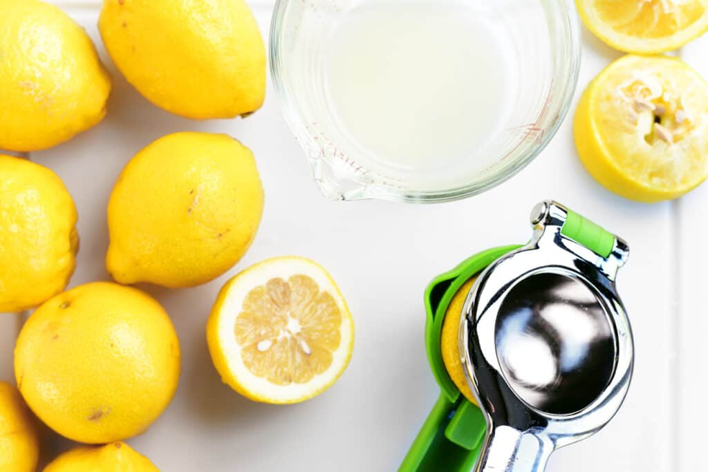 several lemons and a lemon juicing tool on a cutting board