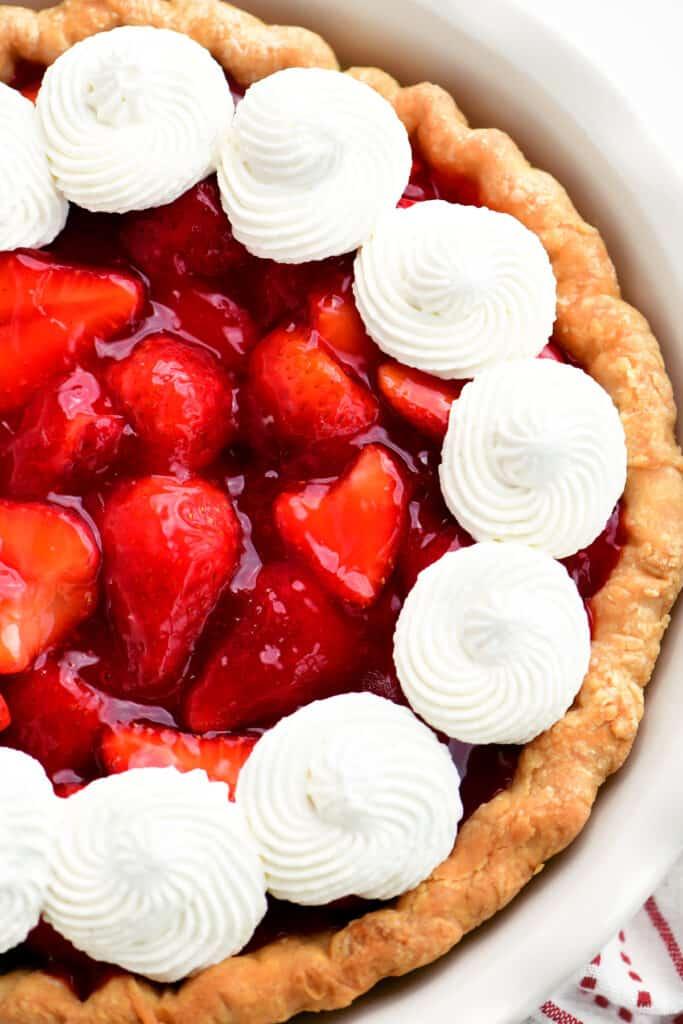 a strawberry pie in a white dish