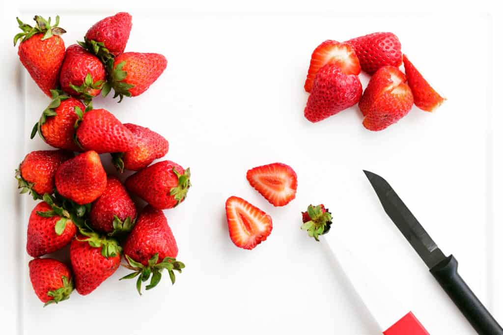 strawberries and knives on a cutting board