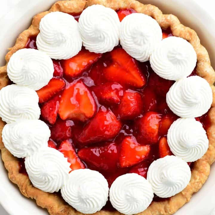 a strawberry pie with whipped cream dollops on top