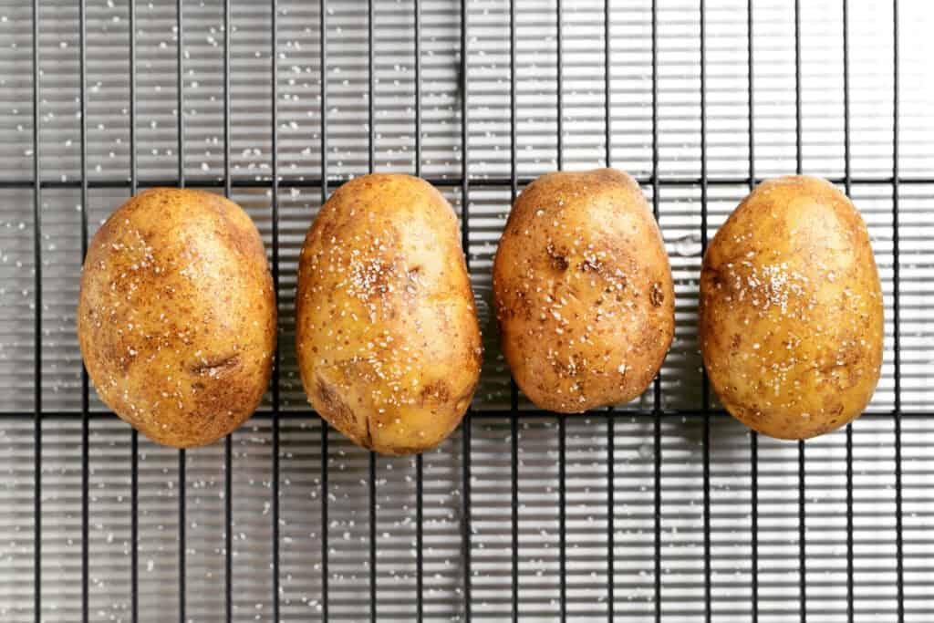 4 potatoes sprinkled with salt arranged on a baking rack