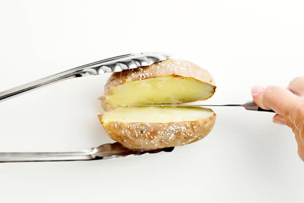 slicing a baked potato in half