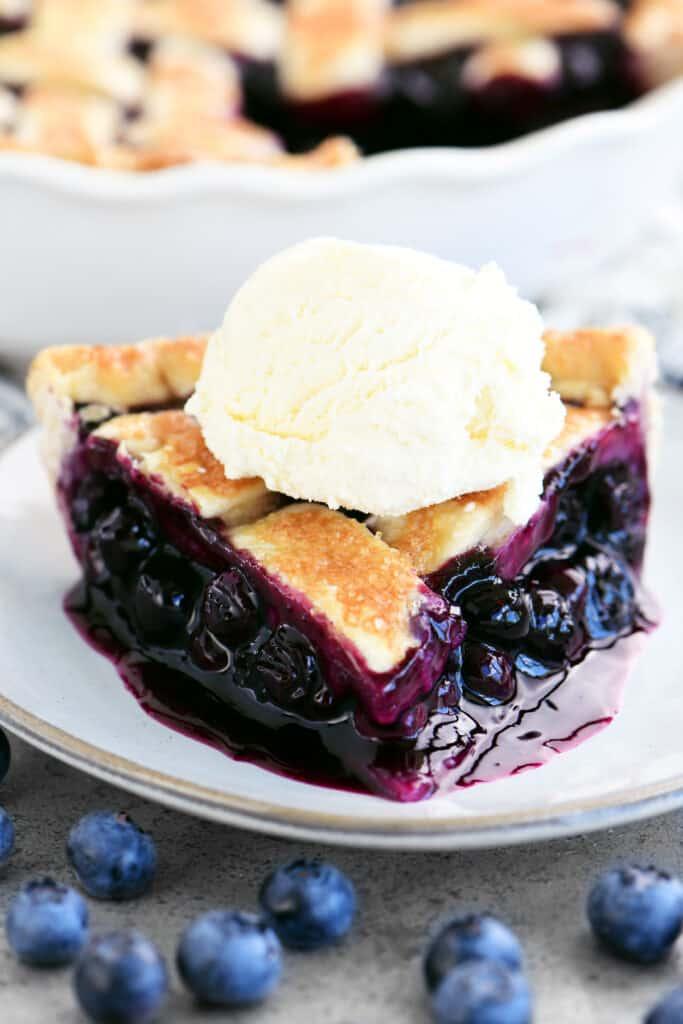 slice of blueberry pie with vanilla ice cream on top