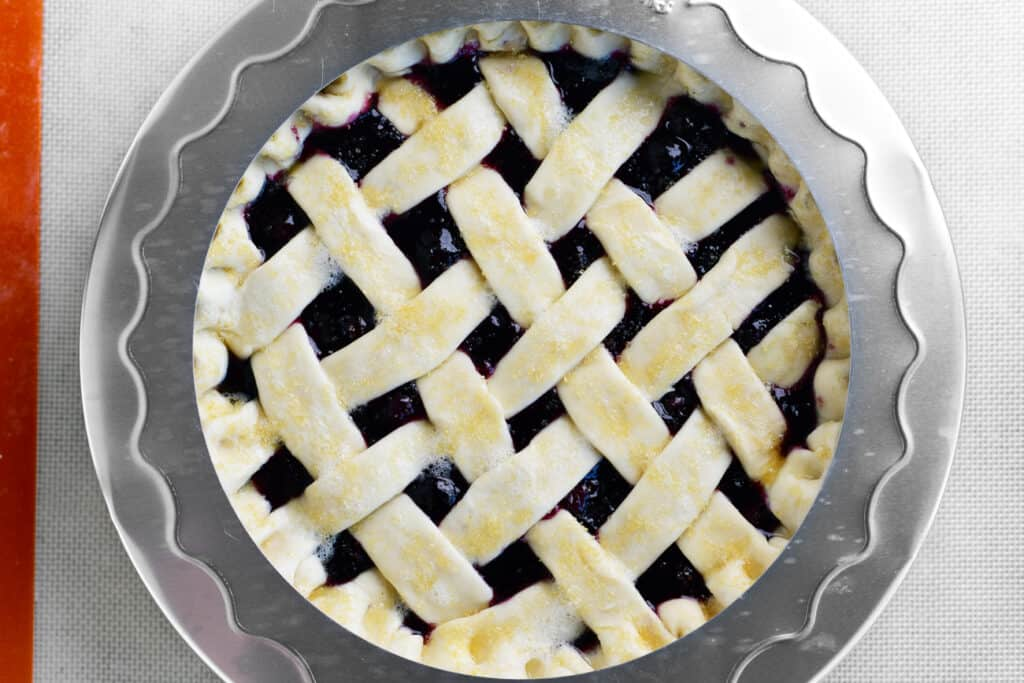 a pie shield on top of the blueberry pie