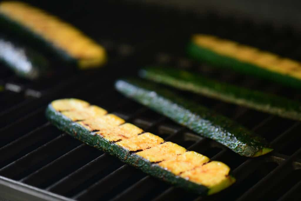 six slices of summer squash on the grates