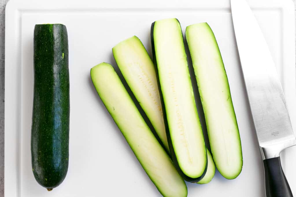 a zucchini, zucchini slices and a knife on a cutting board