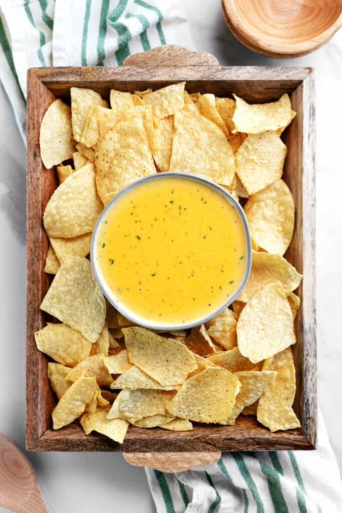 wooden tray with queso in a bowl surrounded by tortilla chips