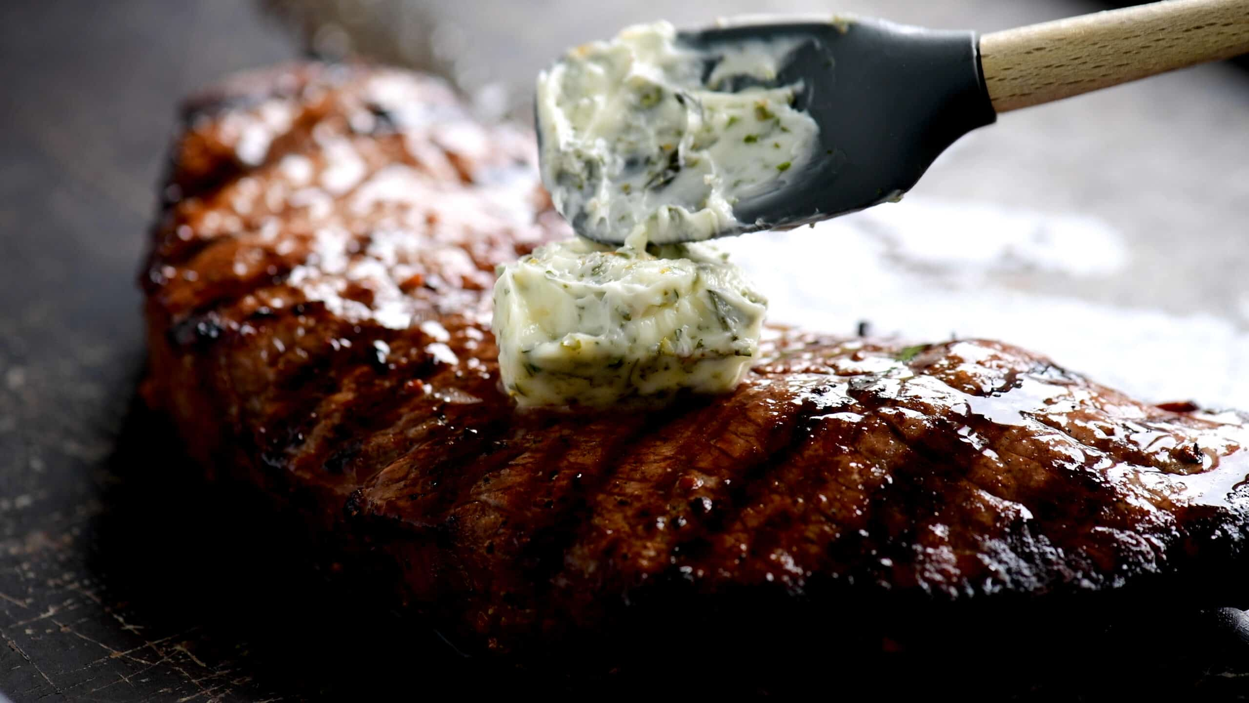 putting herbed butter on a steak