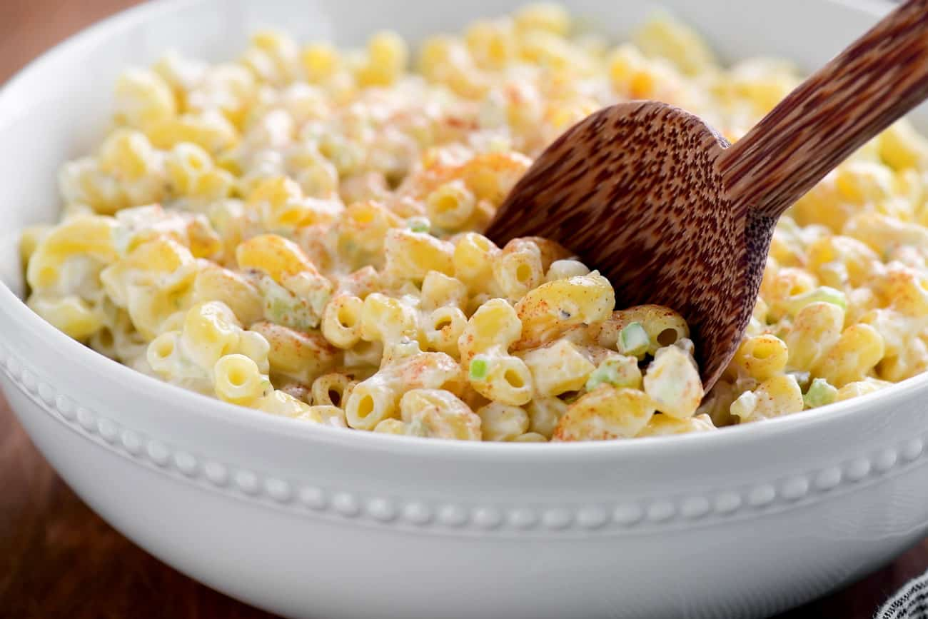 wooden spoon in a bowl of macaroni salad