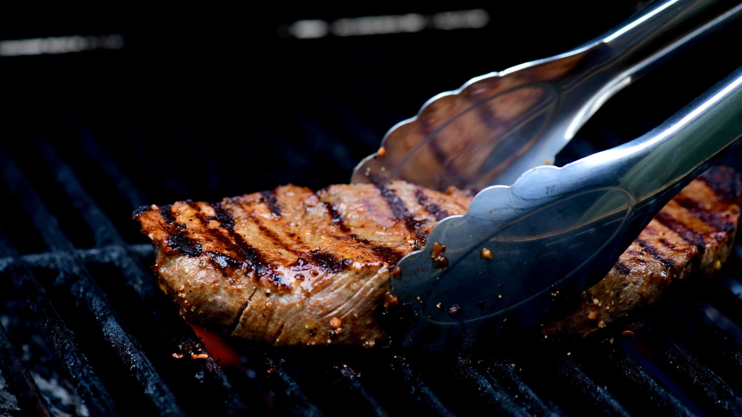 placing a steak on the grill with tongs