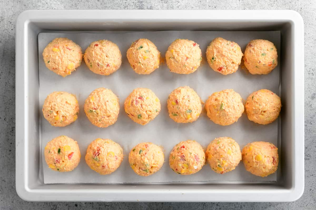 cheese balls lined up in rows in a pan