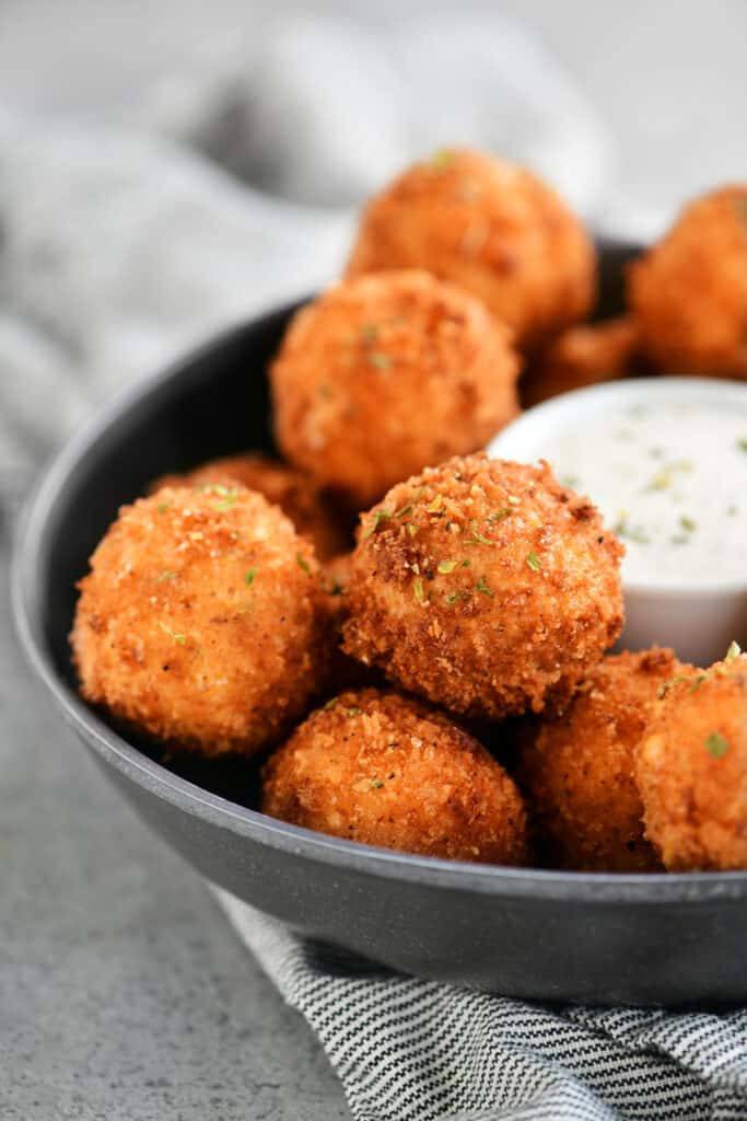 tray of fried corn poppers with a bowl of dip