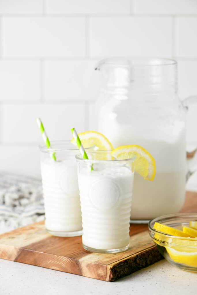 two cups of lemonade whip on a cutting board
