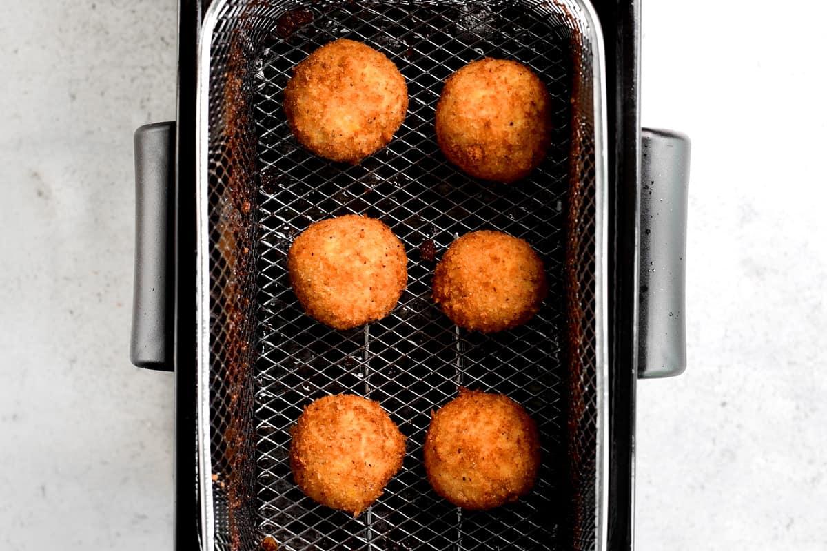 loaded potatoes poppers in deep fryer basket