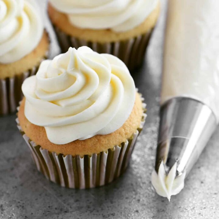 cream cheese buttercream on a cupcake and in a piping bag