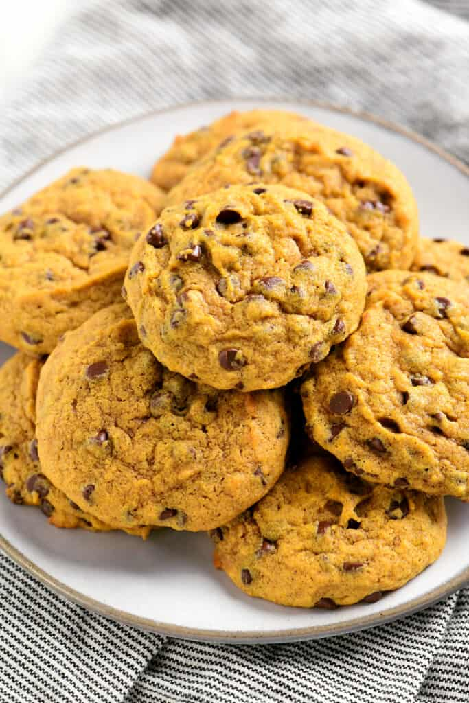 a plate with several pumpkin chocolate chip cookies on it
