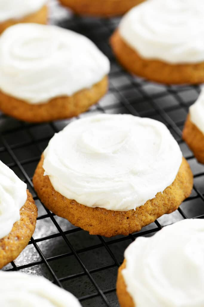 frosted pumpkin cookies on a rack