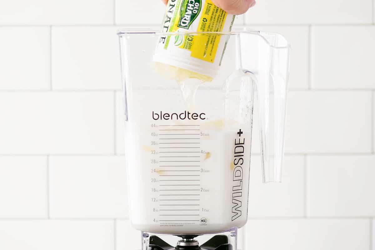 adding frozen lemonade to the blender