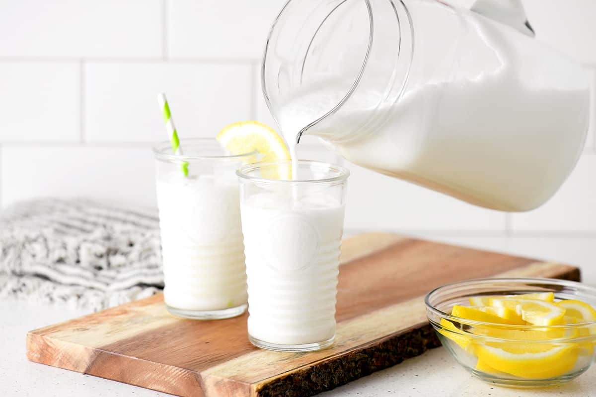 pouring creamy lemonade into a glass on a wood board