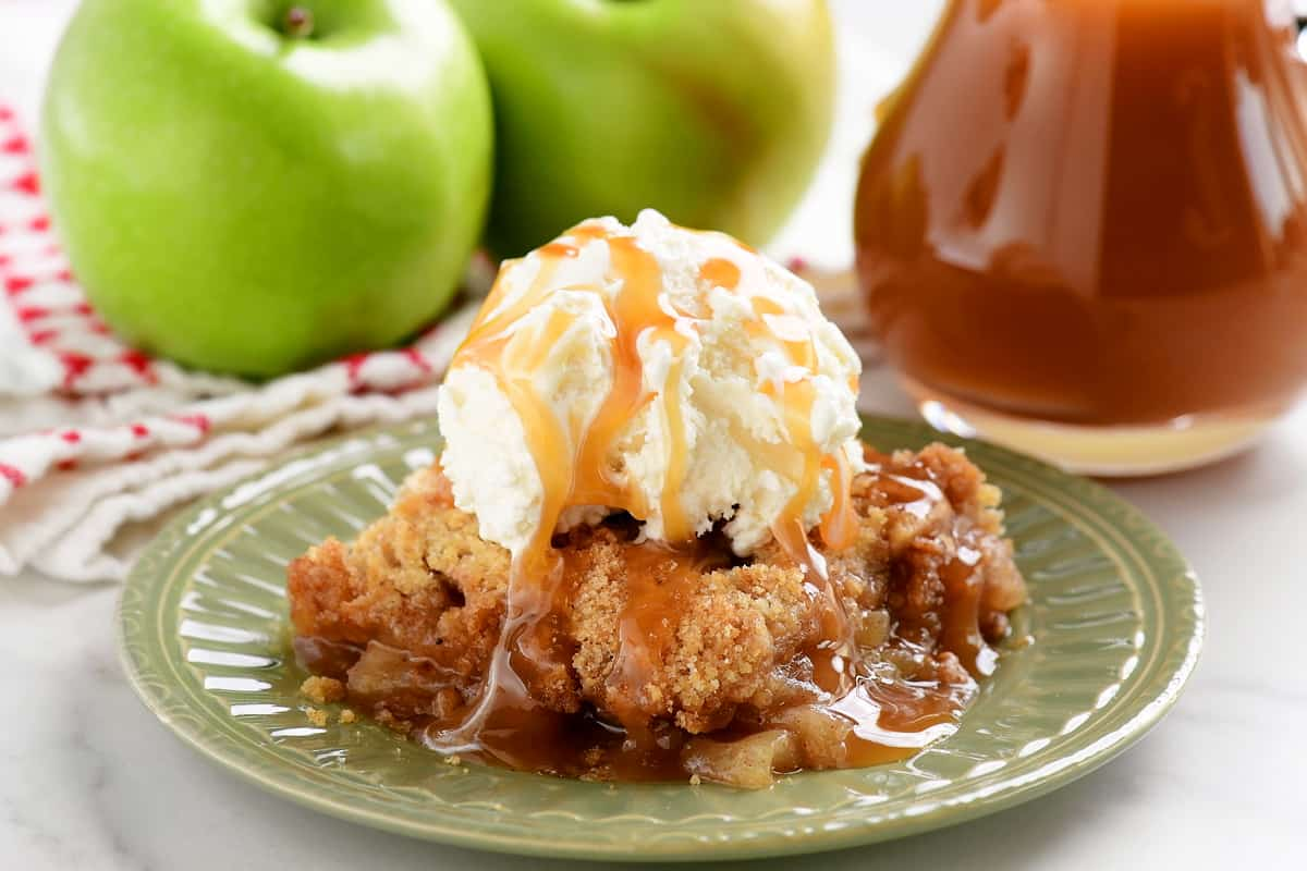 sliced of apple crumble on a green plate with vanilla ice cream on top