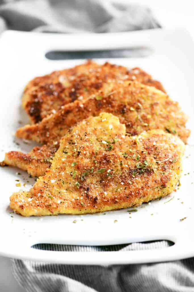 front view of crispy parmesan chicken on a white platter