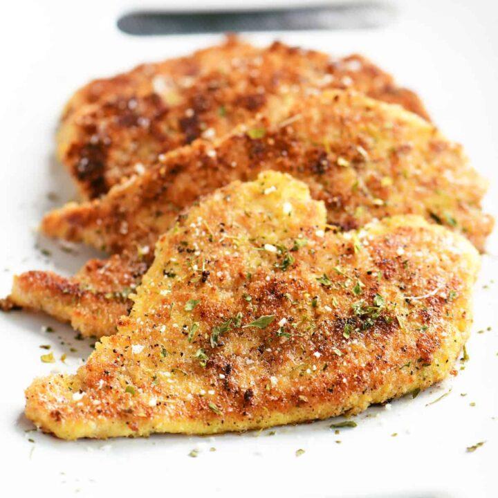 close up of crispy parmesan chicken on a white platter