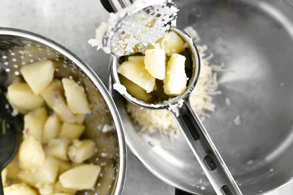 potato chunks in a potato ricer