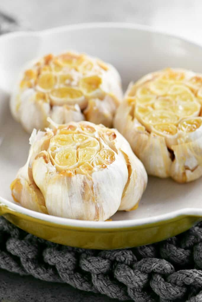 roast garlic heads in a yellow pan